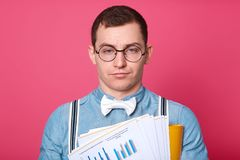 Exhausted unemotional office worker poses isolated over pink background in studio, wearing blue shirt, white bowtie, striped. Suspenders and fashionable stock images