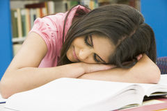 Exhausted university student in library Royalty Free Stock Photography