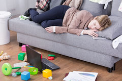 Exhausted after whole day of motherly and office duties. Young mother sleeping in her office clothes on a sofa in a messy living room Stock Image