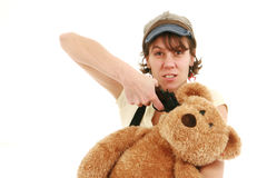 Exhausted woman. Pointing a gun on a teddy bear royalty free stock photography