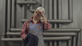 Exhausted woman in apron wiping hands with towel. Exhausted woman in apron and shawl wiping hands with kitchen towel after finishing household chores. Tired stock footage