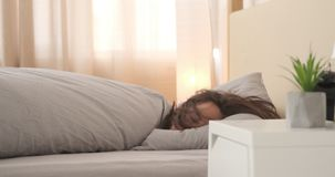 Exhausted woman falling asleep with quilt on bed