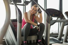 Exhausted woman at the gym wiping off sweat. While smiling stock photo