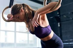 Exhausted Woman on Gymnastic Rings Royalty Free Stock Images