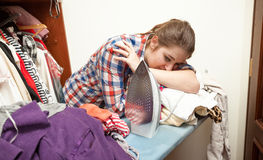 Exhausted woman ironing big pile of clothes Stock Images