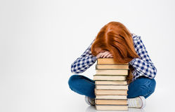 Exhausted woman put head on stack of books and sleeping Royalty Free Stock Photo