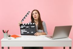 Exhausted woman rolling eyes holding classic black film making clapperboard and working on project while sit at office stock image