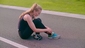 Exhausted woman sitting on asphalt road after running marathon stock footage
