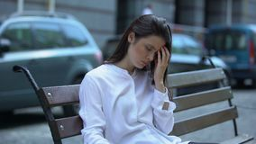 Exhausted woman sitting on bench, suffering from migraine pain, health problem