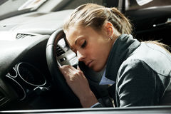 Exhausted woman sleeping in a car Stock Images