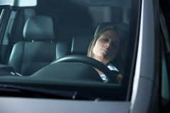 Exhausted woman sleeping in a car Stock Image