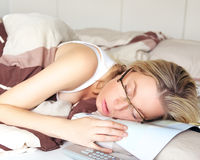 Exhausted woman sleeping in her glasses. Collapsed on top of the document she was reading Stock Image