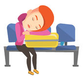 Exhausted woman sleeping on suitcase at airport. Stock Photography