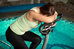 exhausted woman spinning pedals on exercise bike Stock Images