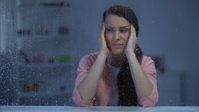 Exhausted woman suffering from head ache behind rainy window, migraine disorder. Stock footage stock video footage