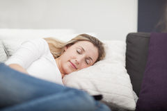 Exhausted woman taking a nap on the sofa Stock Images