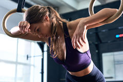 Exhausted Woman Training on Gymnastic Rings Stock Photo