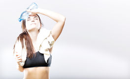 Exhausted woman with water bottle and towel Royalty Free Stock Photos