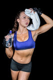 Exhausted woman wiping sweat while holding water bottle Royalty Free Stock Photography