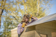 Exhausted woman working on roof of tree house Royalty Free Stock Photos