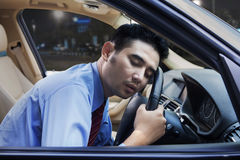 Exhausted worker sleeping in the car Stock Images
