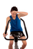 Exhausted after workout on exercise bike royalty free stock photography