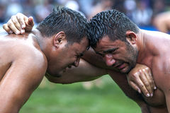 Exhausted wrestlers face each other at the Kemer Turkish Oil Wrestling Festival in Kemer in Turkey. Stock Photos