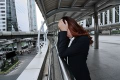 Exhausted young Asian businesswoman with hand on face feeling tired and burnout with his work at the city background. Frustrated s. Tressed business concept Royalty Free Stock Images