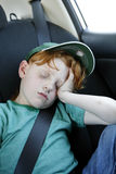 Exhausted young boy sleeping in the car. Stock Photos