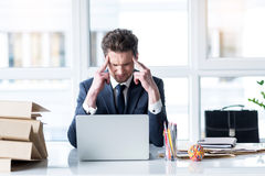 Exhausted young businessman is demonstrating suffering stock photography