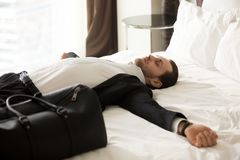 Exhausted businessman laying on bed in hotel room. Royalty Free Stock Image