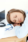Exhausted young businesswoman sleeping on her desk Stock Photos