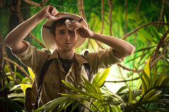 Exhausted young explorer in the jungle. Tired young explorer in the jungle wiping sweat off his forehead Royalty Free Stock Image