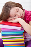 Exhausted young girl asleep on book stack Stock Image
