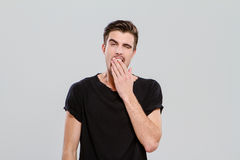 Exhausted young guy yawning and closing mouth by hand Stock Images