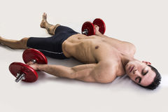 Exhausted young male bodybuilder resting on floor stock photography