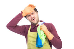 Exhausted young man with apron and gloves holding  cleaning spra Stock Photography