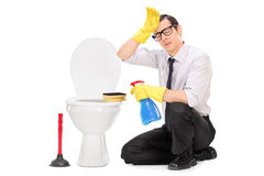 Exhausted young man cleaning a toilet Stock Photos