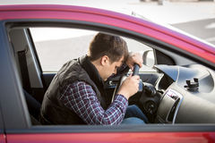 Exhausted young man sleeping on drivers seat while driving a car Stock Photo