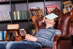 Exhausted young man sleeping in a library. Relaxing in a comfortable leather armchair with an open book over his eyes Royalty Free Stock Photography