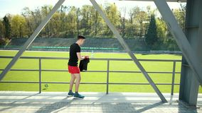 Exhausted Young Man Wiping Sweat With Towel From His Forehead After Exercising. Tired Sportswoman Drinking Water And. Resting Near Stadium. Concept Sorowako stock video footage