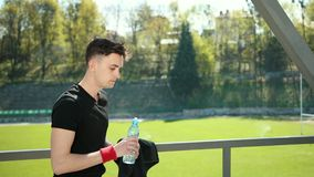 Exhausted Young Man Wiping Sweat With Towel From His Forehead After Exercising. Tired Sportswoman Drinking Water And. Resting Near Stadium. Concept Sorowako stock video