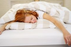 Exhausted woman sleeping spread out on the bed royalty free stock photography