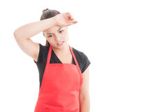 Exhausted young seller with red apron at work Royalty Free Stock Photos