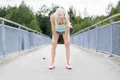 Exhausted young woman catching her breath after a long run Stock Image