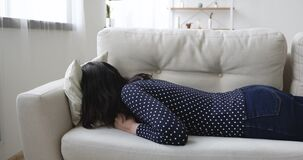 Exhausted young woman flopped down on sofa face in cushion