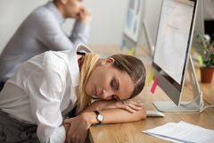 Exhausted young woman taking break to rest sleeping at workplace stock photo