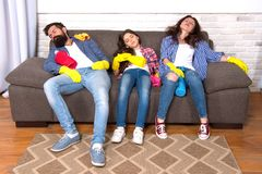 Exhausting cleaning day. Family mom dad and daughter with cleaning supplies sit on couch. Family care about cleanliness. Finish cleaning. Cleaning all day royalty free stock photo