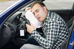 Exhausting man is sleeping in a car. Stock Photos