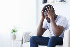 African-american man suffering from headache at home. Exhausting migraine. Young african-american man suffering from headache at home, copy space royalty free stock image